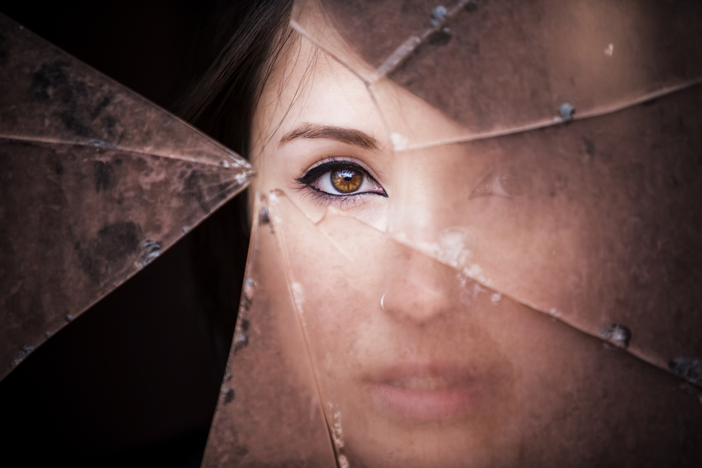 woman looking out behind shattered glass