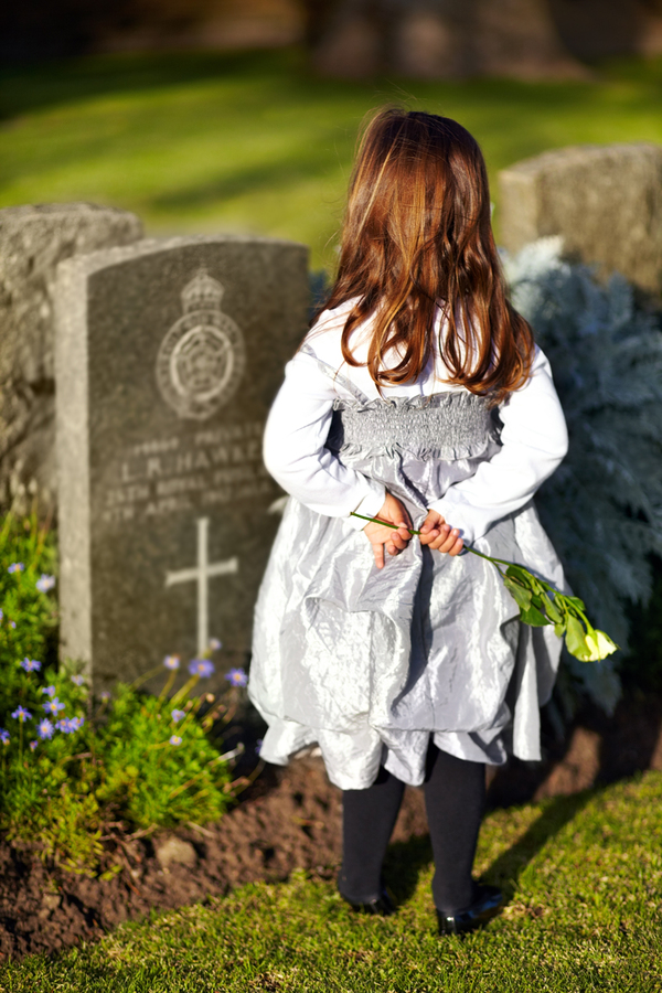 girl grieving at grave