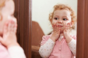 Baby aware of herself in a mirror